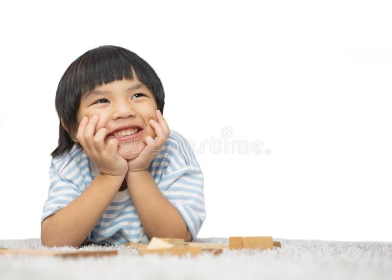 Petit garçon de sourire de pensée se couchant sur le plancher et recherchant Petit garçon mignon se trouvant sur le plancher d'is image libre de droits