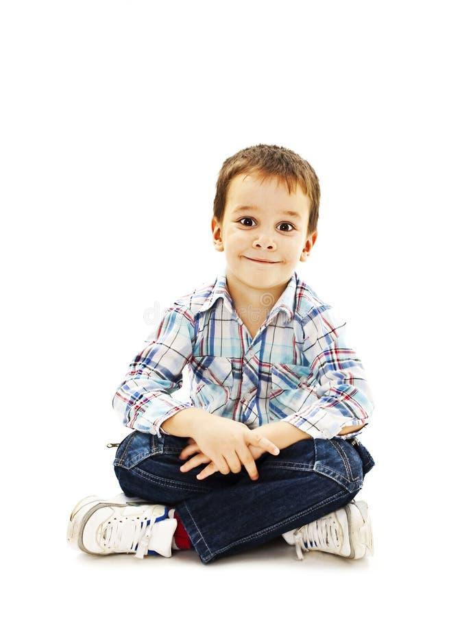 Petit garçon de sourire s'asseyant sur le plancher dans des jeans photo stock