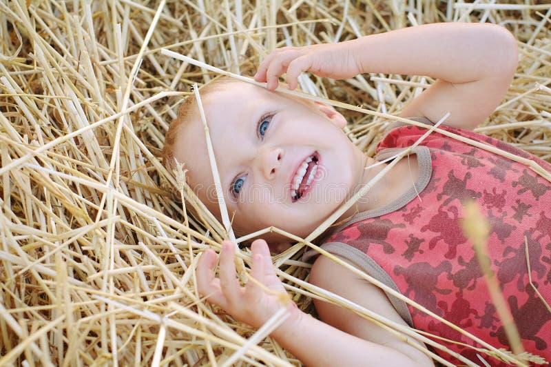 Petit garçon de sourire sur une pile de foin Enfant heureux dans le domaine photos libres de droits