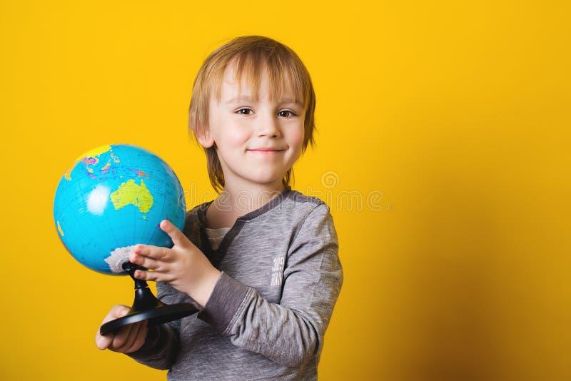 Petit garçon de sourire tenant le globe dans des mains - d'isolement sur le jaune photo stock
