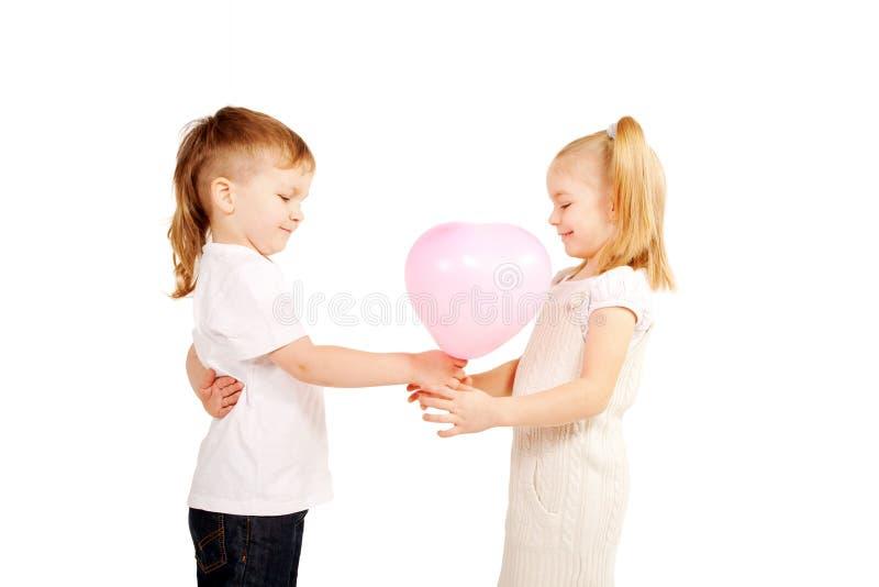 Petit garçon donnant à fille un coeur, concept du jour de valentine. photographie stock