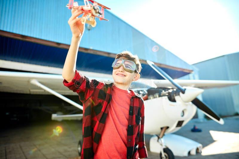 Petit garçon doux avec l'avion de jouet jouant dehors un beau jour ensoleillé d'été photos stock