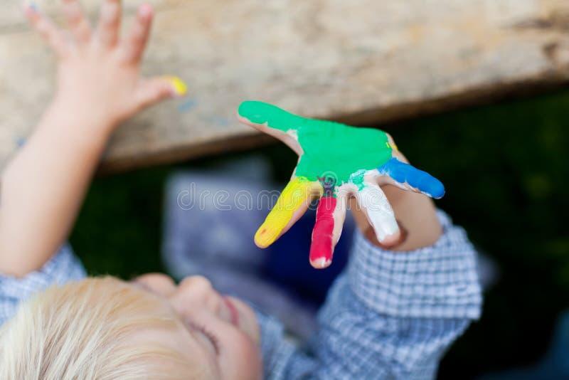 Petit garçon doux montrant sa main colorée photos stock