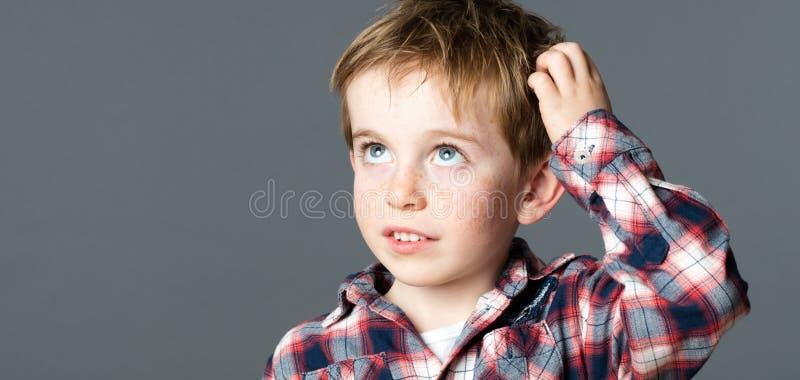 Petit garçon doux rayant sa tête pour l'imagination images stock