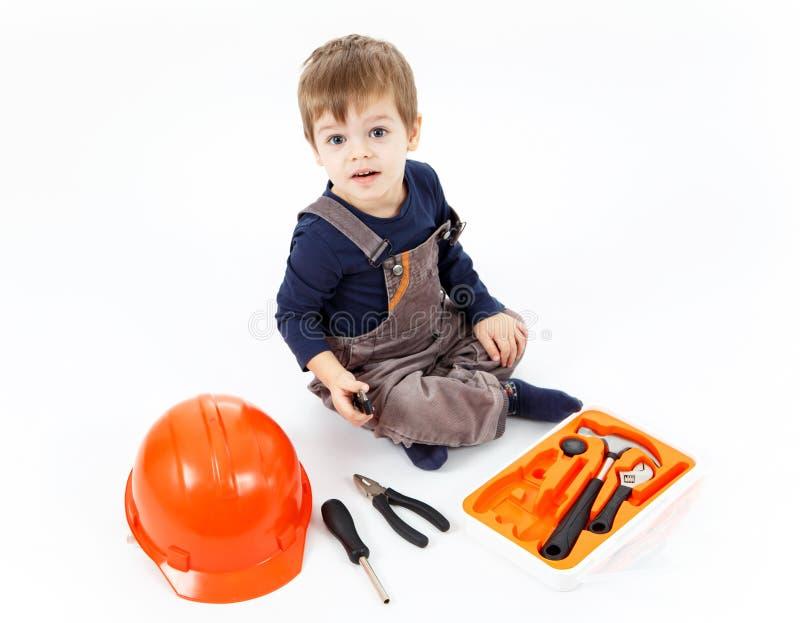 Petit garçon drôle avec la trousse à outils sur le fond blanc photos stock