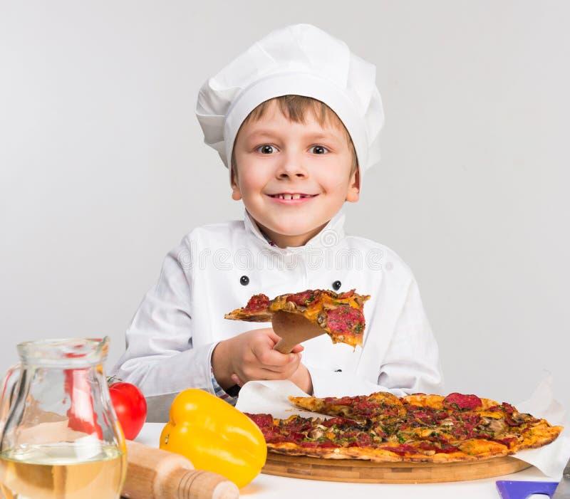Petit garçon drôle tenant un morceau de pizza savoureuse images stock