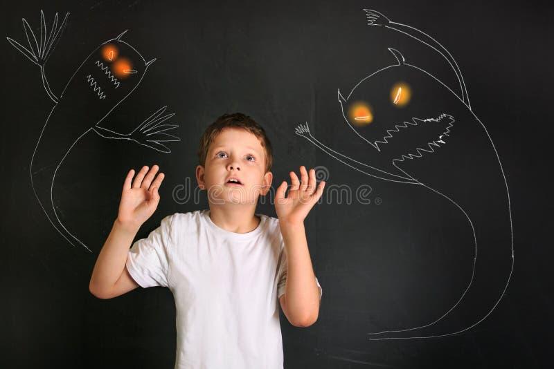 Petit garçon effrayé effrayé des monstres de nuit photographie stock libre de droits