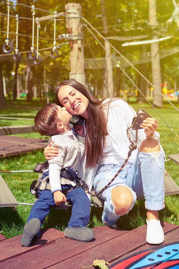 Petit garçon embrassant sa mère photo stock