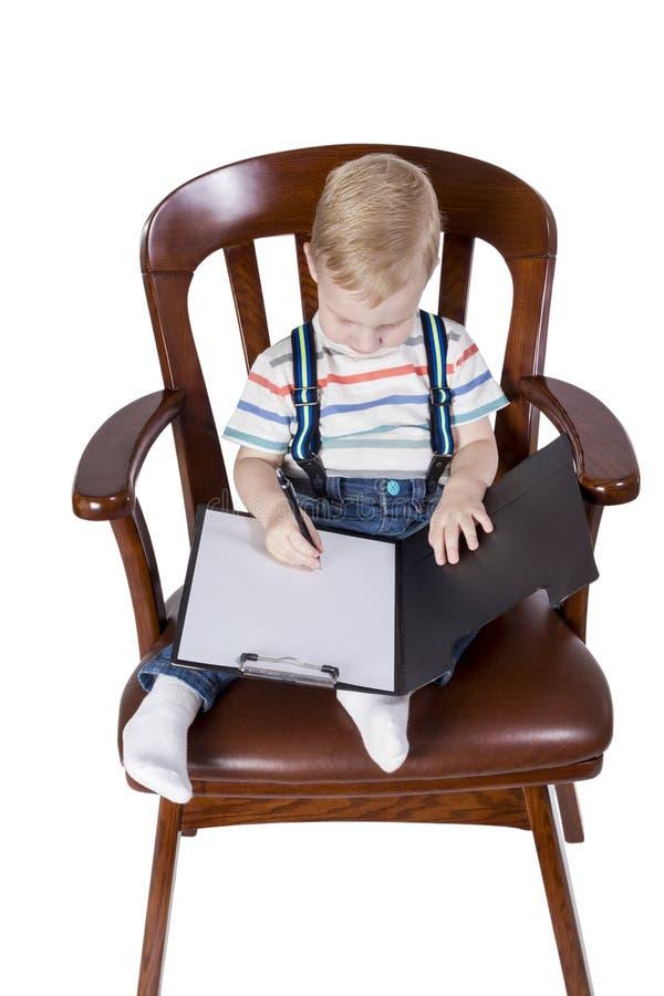 Petit garçon en tant que directeur dans la chaise image stock