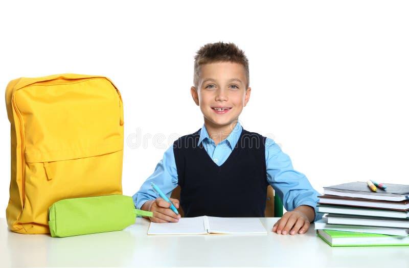 Petit garçon en uniforme faisant une affectation au bureau sur fond blanc photographie stock