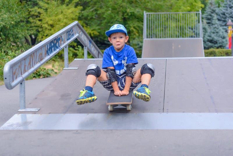 Petit garçon enthousiaste essayant sa nouvelle planche à roulettes photos libres de droits