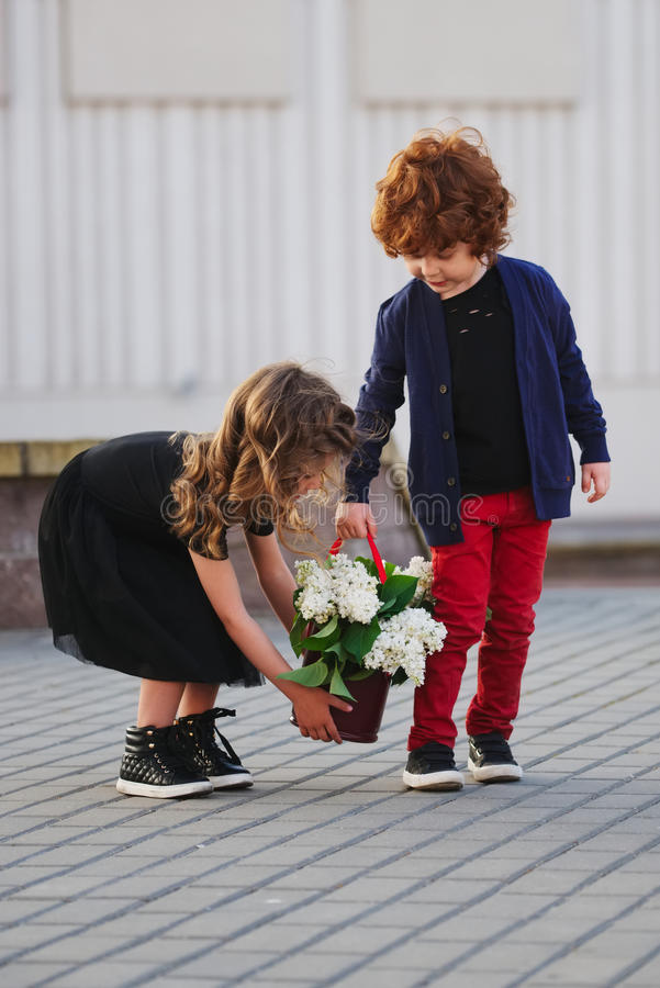 Petit garçon et fille avec le grand bouquet lilas photos libres de droits