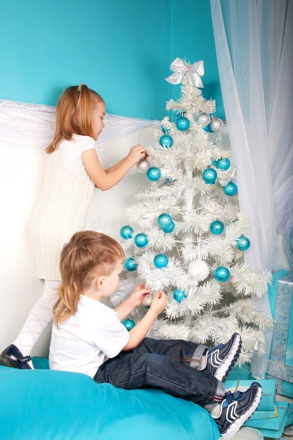 Petit garçon et fille décorant l'arbre de Noël photos stock