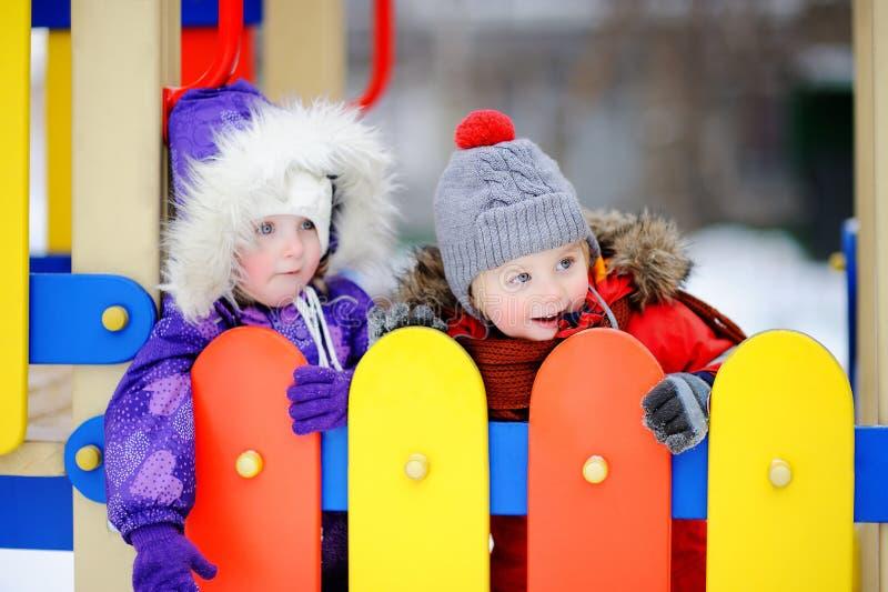 Petit garçon et fille dans des vêtements d'hiver ayant l'amusement dans le terrain de jeu d'extérieur photos libres de droits