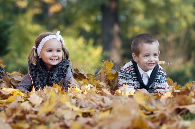 Petit garçon et fille fixant sur l'herbe images stock