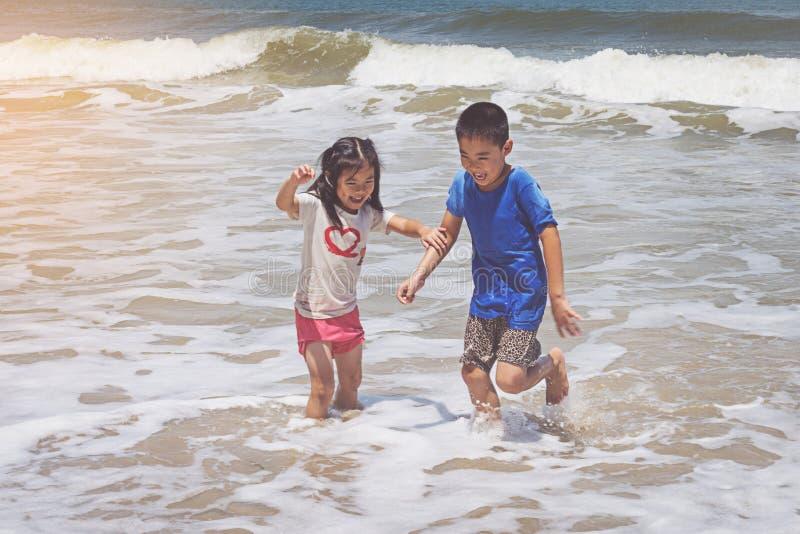 Petit garçon et fille jouant sur la plage photo libre de droits