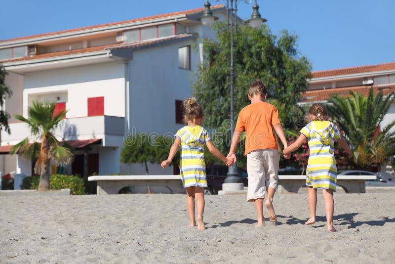Petit garçon et filles marchant sur la plage images libres de droits