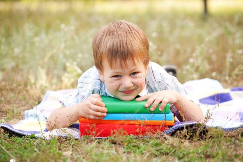 Petit garçon et livres dehors. De nouveau à l'école. image libre de droits