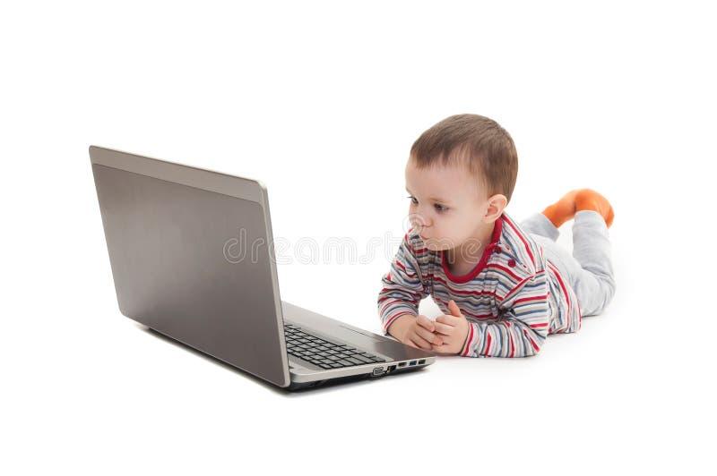 Petit garçon et ordinateur portable d'isolement photos stock