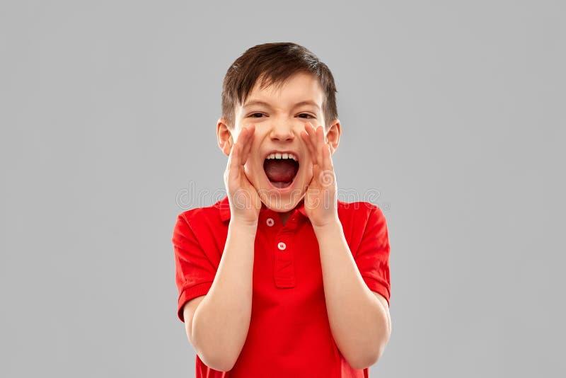 Petit garçon fâché dans le T-shirt rouge de polo criant image libre de droits