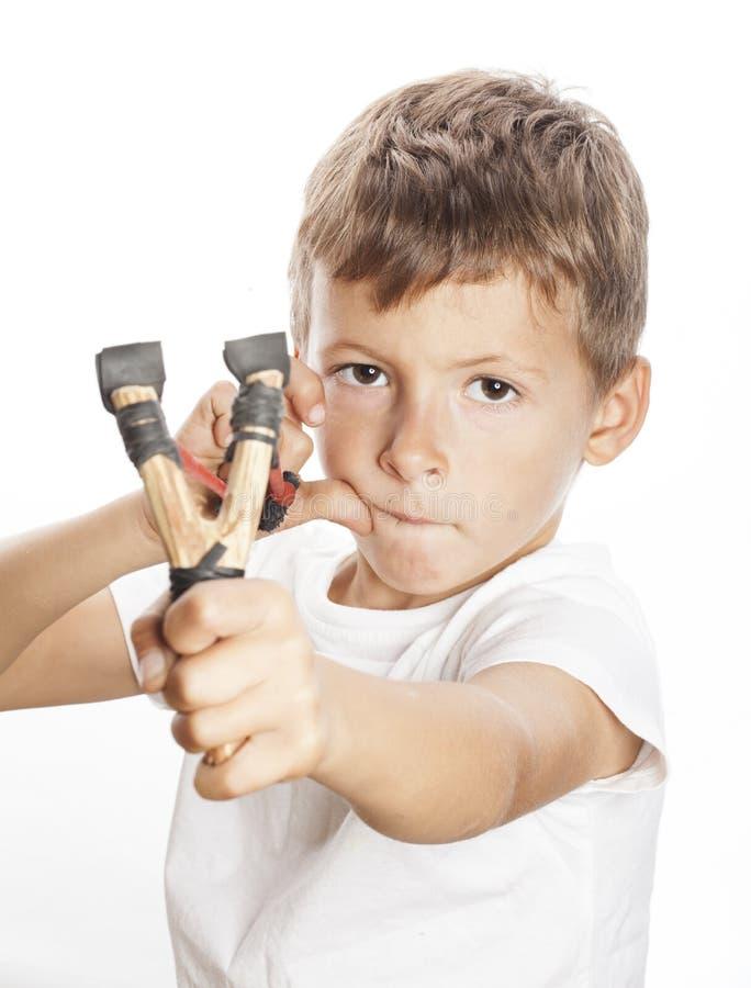 Petit garçon fâché mignon avec la fronde d'isolement photos stock