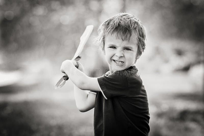 Petit garçon fâché, tenant l'épée, brillant avec un visage fou au photos libres de droits