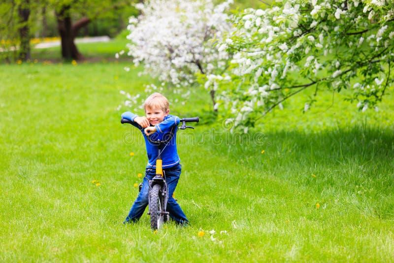 Petit garçon faisant du vélo au printemps le jardin photo stock
