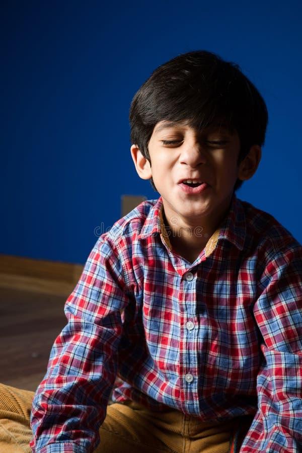 Petit garçon faisant les visages drôles images libres de droits