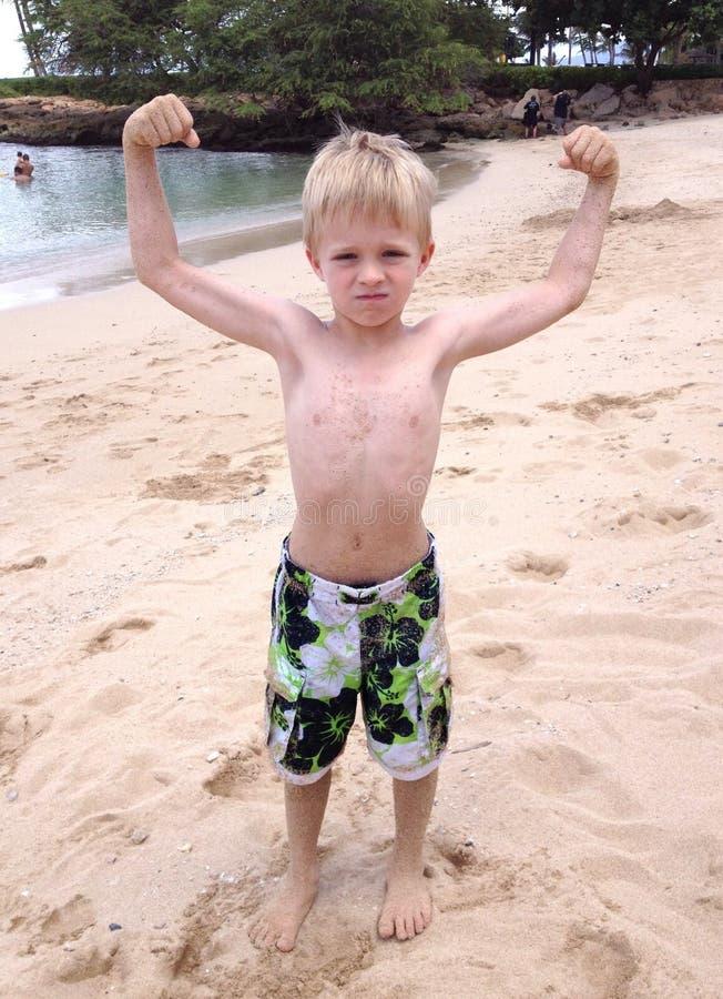 Petit garçon fort à la plage photo stock