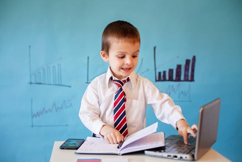 Petit garçon futé, travaillant sur l'ordinateur et prenant des notes images stock