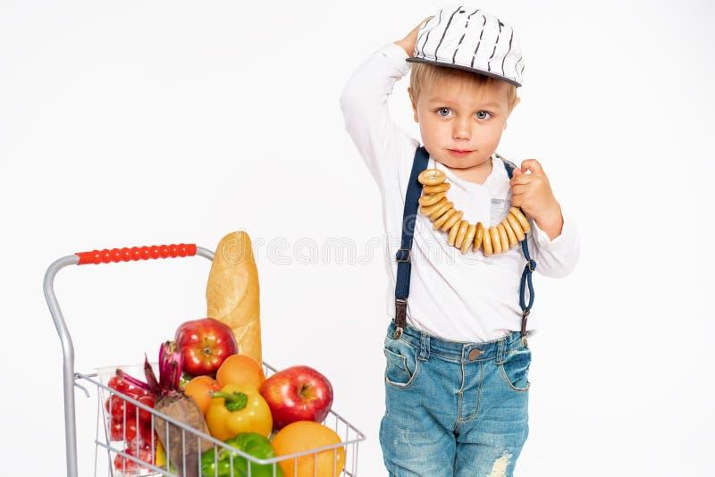 Petit garçon gai dans des vêtements sport se tenant dans le studio avec le panier sain de nourriture Achats, remise, concept de v image libre de droits