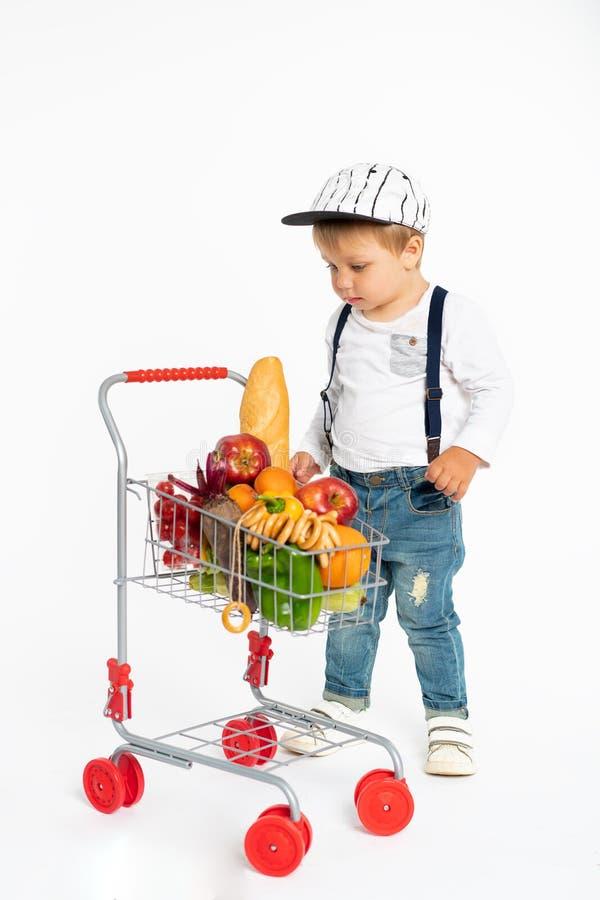 Petit garçon gai dans des vêtements sport se tenant dans le studio avec le panier sain de nourriture Achats, remise, concept de v photographie stock