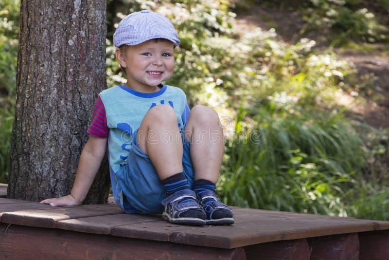 Petit garçon gai se reposant dans une forêt verte d'été photo libre de droits