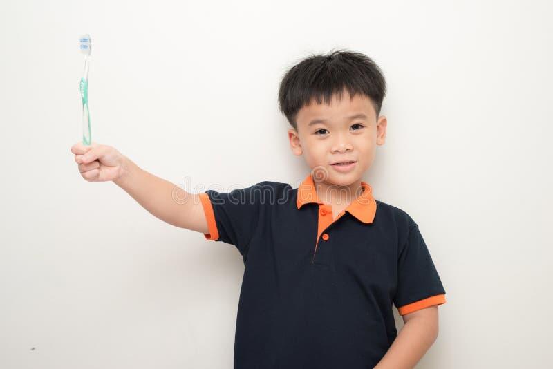 Petit garçon gai tenant une brosse à dents au-dessus du fond blanc, photos stock