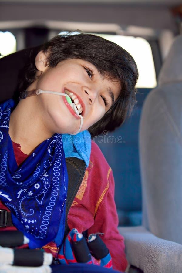 Petit garçon handicapé s'asseyant dans le carseat à l'intérieur du véhicule image libre de droits