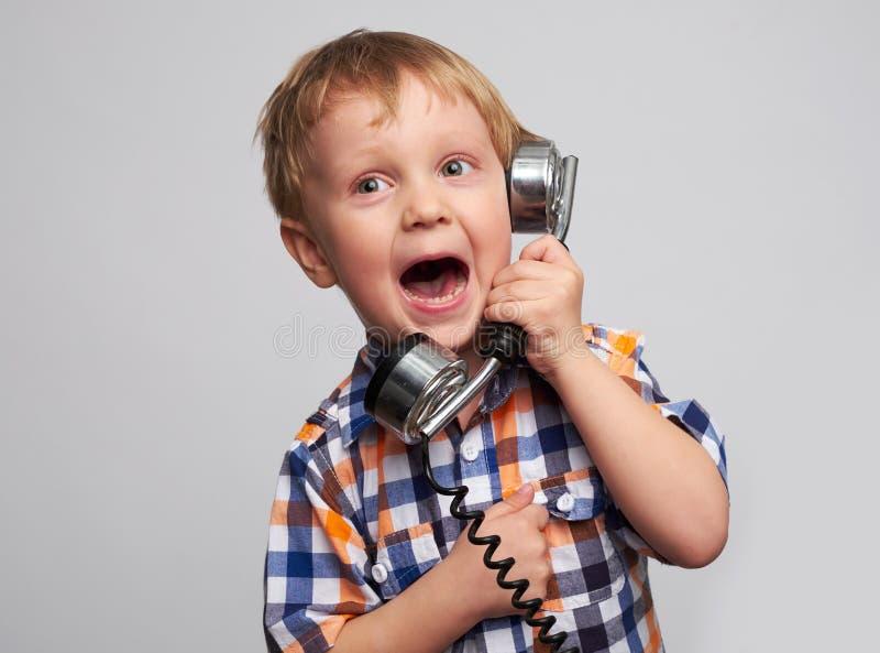 Petit garçon heureux adorable avec le téléphone photo stock