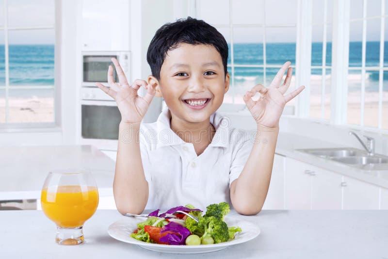 Petit garçon heureux avec de la salade dans la cuisine image libre de droits