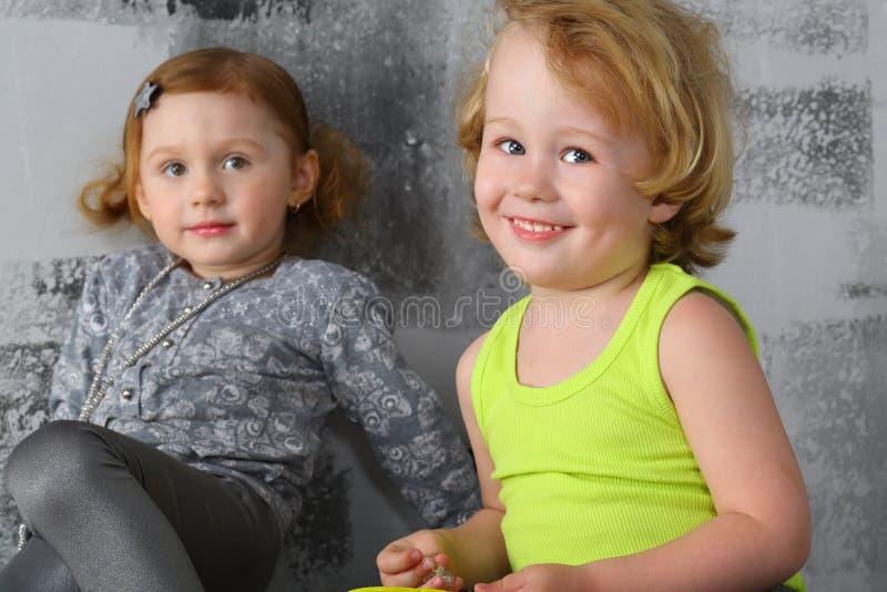 Petit garçon heureux avec la fille près du mur gris image stock
