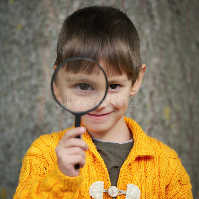 Petit garçon heureux avec la loupe photo stock