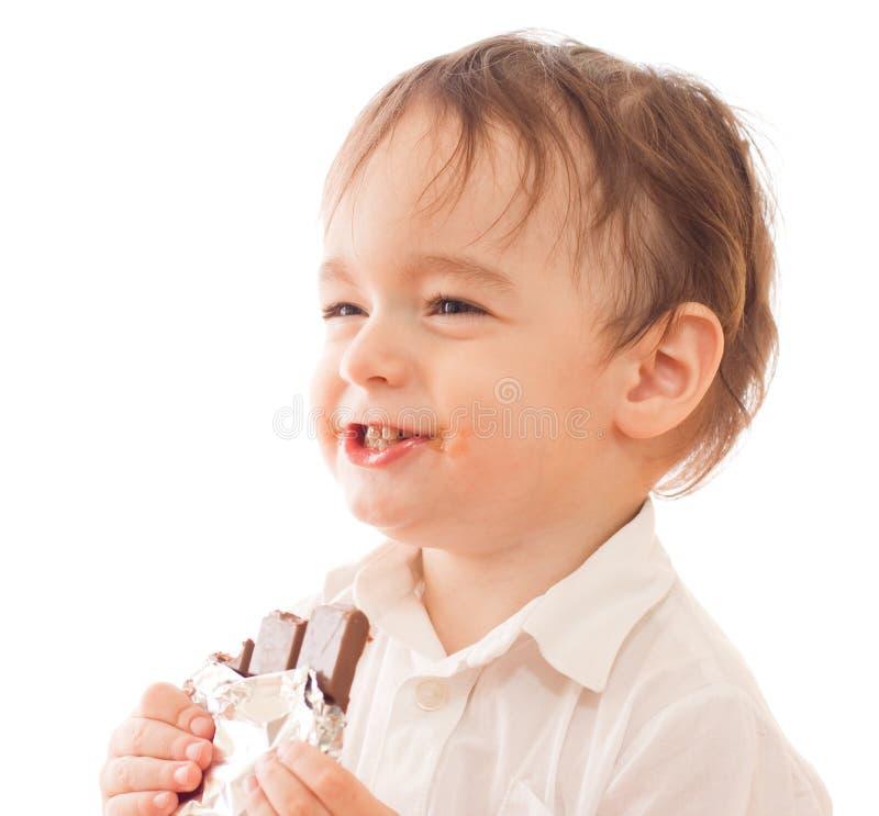 Petit garçon heureux avec le bar du chocolat dans sa main photographie stock libre de droits