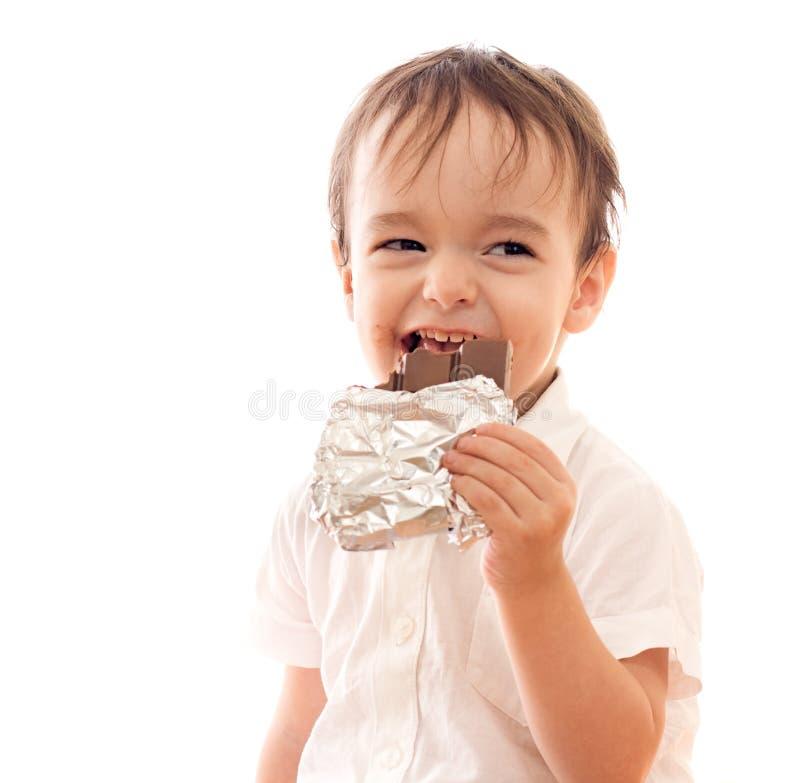 Petit garçon heureux avec le bar du chocolat dans sa main image stock