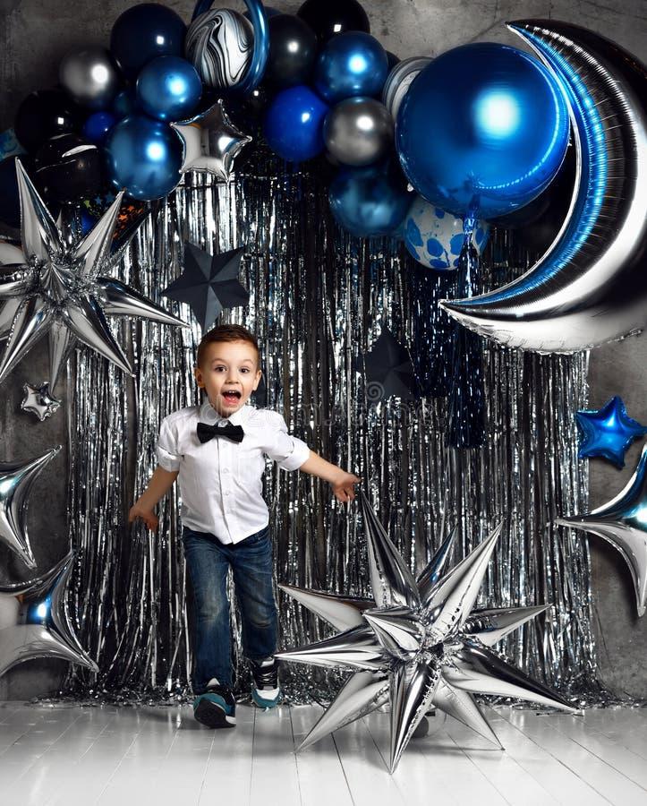 Petit garçon heureux avec les ballons métalliques argentés et bleus de lune pour la partie de l'espace d'anniversaire avec le tex photographie stock libre de droits