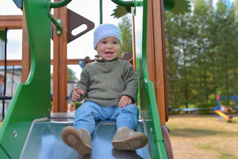 Petit garçon heureux d'enfant en bas âge ayant l'amusement glissant sur le terrain de jeu photographie stock libre de droits