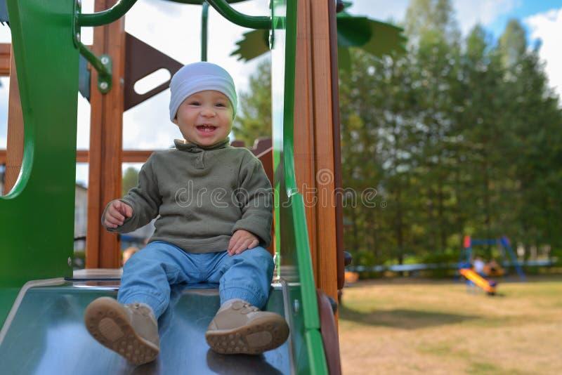 Petit garçon heureux d'enfant en bas âge ayant l'amusement glissant sur le terrain de jeu photo stock