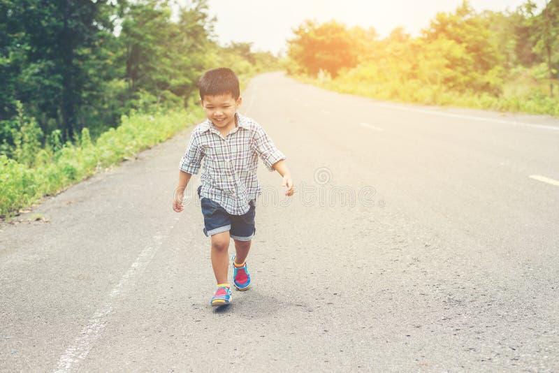 Petit garçon heureux dans le mouvement, smiley fonctionnant sur la rue photos libres de droits