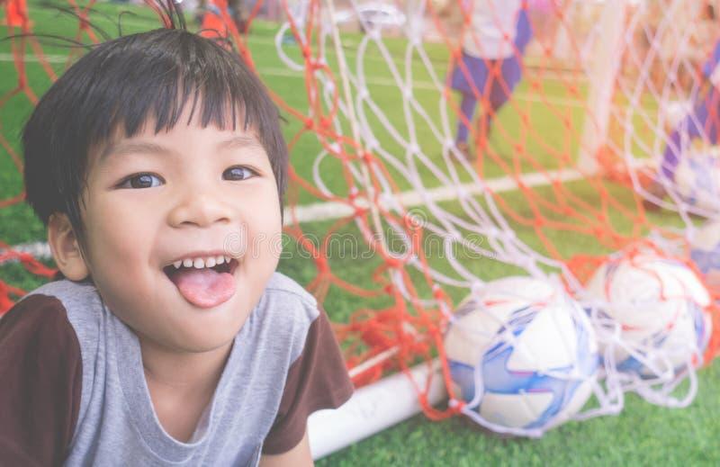 Petit garçon heureux derrière le but dans la formation du football images libres de droits