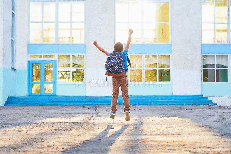 Petit garçon heureux, fortement sauté avec joie, le début de l'année scolaire l'enfant heureux va à l'école primaire attitude pos image libre de droits