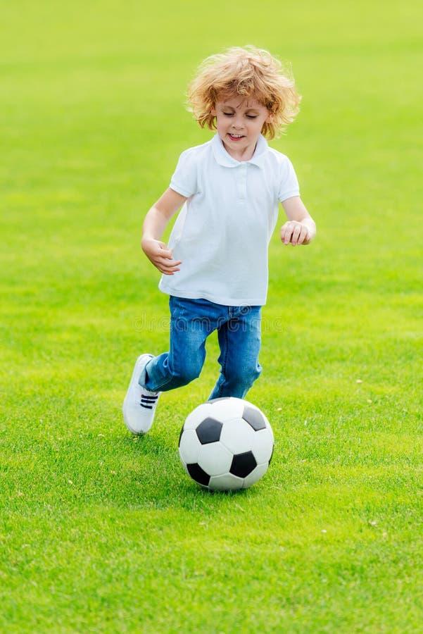 petit garçon heureux mignon jouant le football sur l'herbe verte photos stock