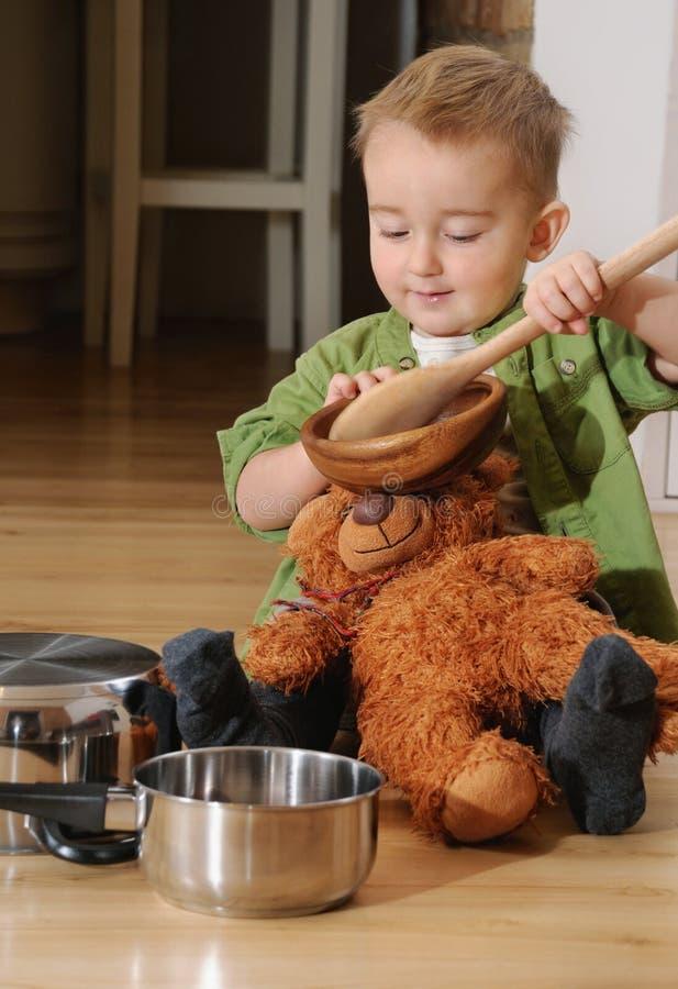 Petit garçon heureux s'asseyant sur le plancher de cuisine jouant avec des pots photos stock