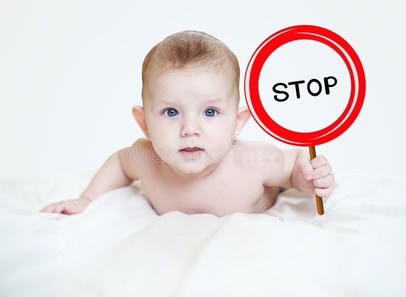Petit garçon intelligent retenant un signe photos stock